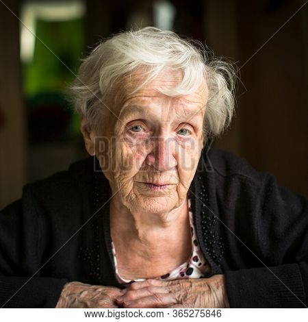 Close-up portrait of old woman, sitting in the her home.