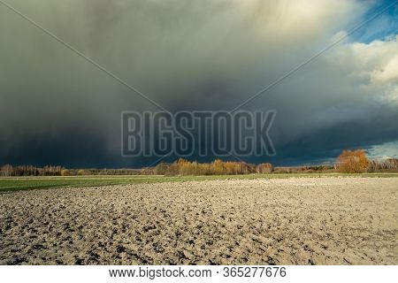 Huge Dark Hail Cloud Over The Plowed Field, View On A Spring Sunny Day