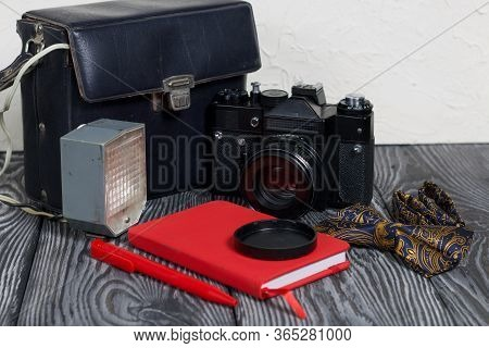 Photographer Accessories. Camera, Flash, Bow-tie, Notebook And Pen. On Brushed Pine Boards.