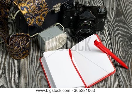Photographer Accessories. Camera, Flash, Tie, Notebook And Pen. On Brushed Pine Boards.