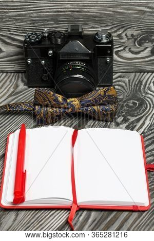 Photographer Accessories. Camera, Bow-tie, Notebook And Pen. On Brushed Pine Boards.