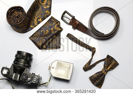 Retro Camera With Flash. Photographer Accessories: Belt, Bow-tie And Tie. Shot From Above, On A Whit