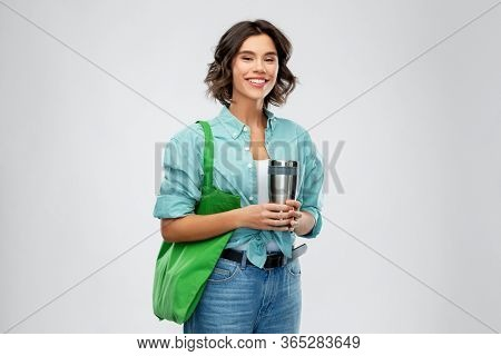 sustainability, eco living and people concept - portrait of smiling young woman with green reusable canvas bag for food shopping and tumbler or thermo cup over grey background