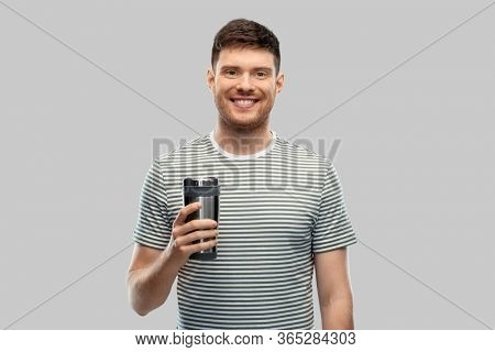 eco living and sustainability concept - happy smiling young man in striped t-shirt with thermo cup or tumbler for hot drinks over grey background