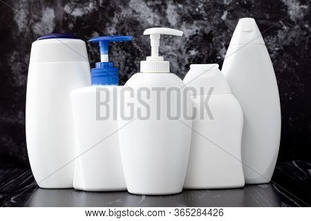 White Plastic Bottles Of Liquid Soap, Shampoo And Shower Gel. Hygiene Concept. Toiletries On Black M