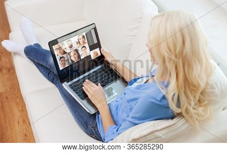 technology, remote job and online communication concept - young woman with laptop computer sitting on couch at home and having video call with friends or colleagues