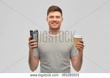 eco living and sustainability concept - smiling young man in striped t-shirt comparing thermo cup or tumbler with disposable paper coffee cup over grey background