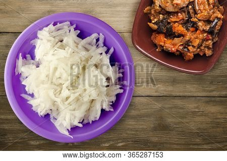 Daikon On Brown Wooden Background. Daikon On Purple Plate With Vegetarian Salad Top View.