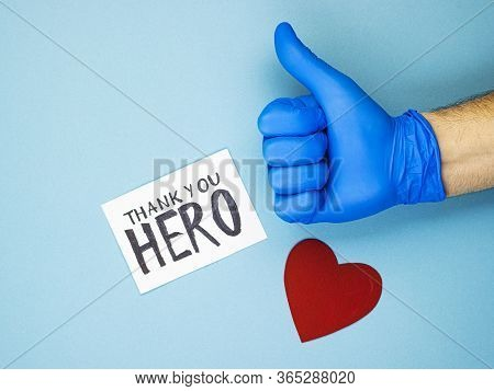 A Hand With A Raised Thumb In A Medical Glove, A Red Heart And The Inscription Thank You To The Hero