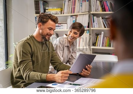 Successful business man and smiling businesswoman discussing while using digital tablet in office. Happy business team working in new company. Mature businessman showing data to business woman.