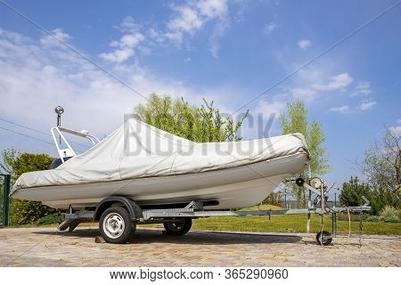 Big Modern Inflatable Motorboat Ship Covered With Grey Or White Protection Tarp Standing On Steel Se