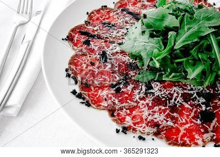 Carpaccio With Parmesan, Balsamic Vinegar On A Plateau On The Table