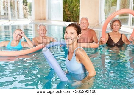 Young woman as a therapist for aqua-gym in rehab with seniors group