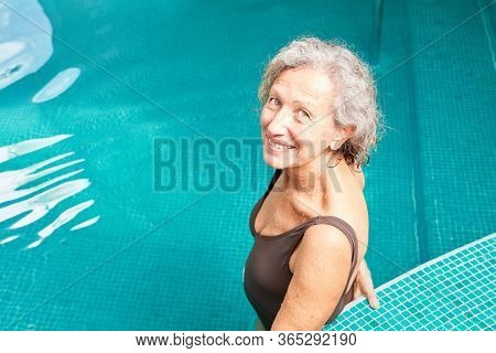 Vital senior woman stands smiling in the swimming pool and exercises her fitness