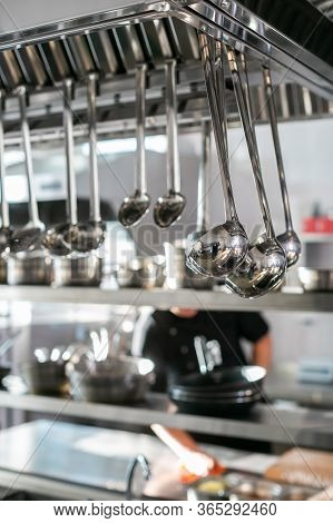 Shiny Stainless Ladles Hanging In Kitchen. Restaurant Kitchen With Hanging Set Of Shiny Ladles