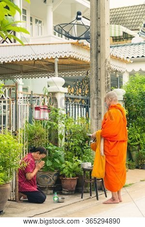 Nonthaburi, Thailand- May 08, 2020 : An Old Asian Woman Is Sitting And Respecting Buddhist Monks Aft