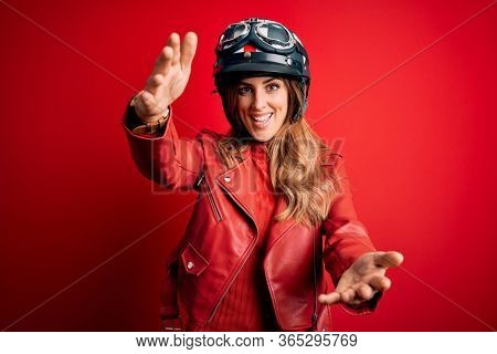 Young beautiful brunette motrocyclist woman wearing moto helmet over red background looking at the camera smiling with open arms for hug. Cheerful expression embracing happiness.