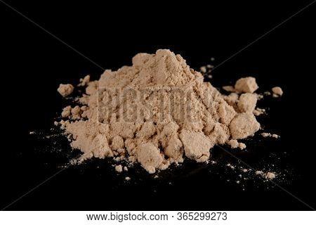 Brown powder looking like street heroin shot on black surface