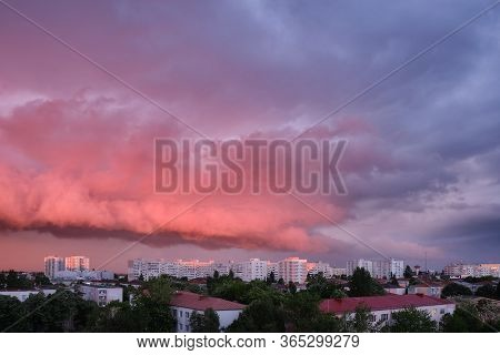 Pink And Purple Storm Clouds At Sunset, In Bucharest, Romania, Contrasting With Bright Exterior Buil