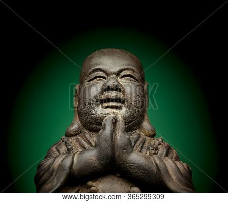 A Small Replica Statue Of The Buddha With A Green Background.  Green Symbolizing Cleanliness And Pur