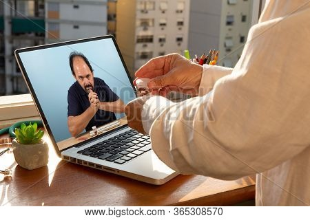 Doctor Talks To His Patient Via Telemedicine During The Coronavirus Pandemic At His Front-to-window