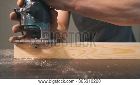 Worker Bevel Wooden Board. Milling Cutter And Sawdust, Closeup. Professional Carpentry Concept.