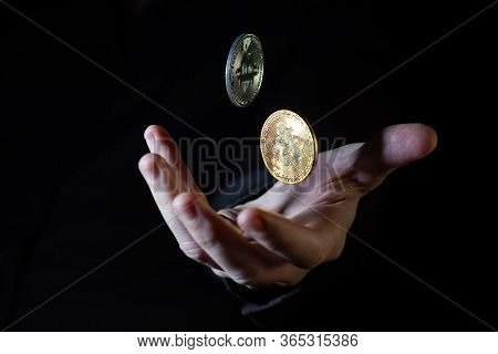 Male Hand Throwing Two Bitcoins Up In The Air On Black Background - Closeup