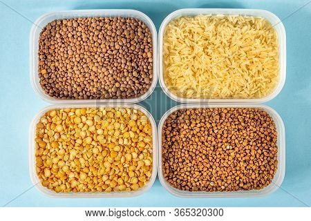 Raw Rice, Buckwheat And Dry Peas In Plastic Containers On Blue Background
