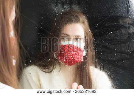 Studio Portrait Of A Woman In A Protective Mask With Red Rhinestones, Looks In The Mirror