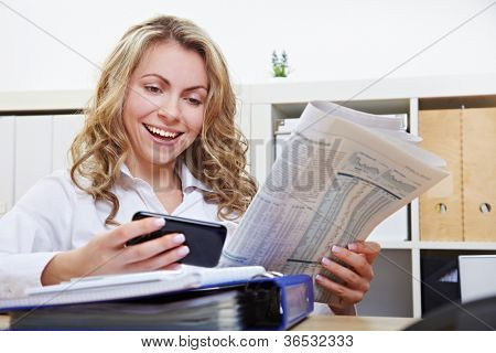 Happy business woman with smartphone reading financial section of newspaper in the office