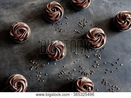 Dark Chocolate Cupcakes And Cocoa Nibs On Dark Background. Sweet Food Concept.