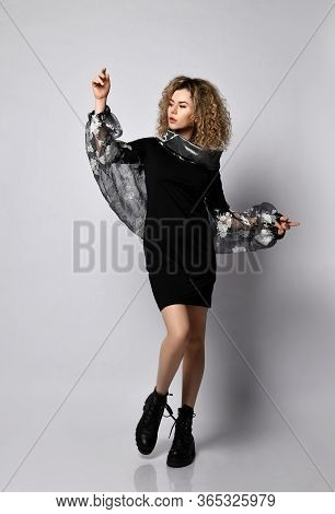 Blonde Curly Woman In Black Stylish Dress With Voluminous Sleeves And Brutal Boots Is Dances With He