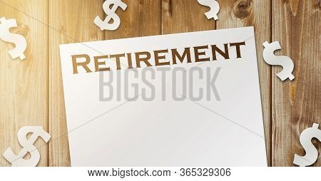 Word Retirement On A Copybook Page And Paper Dollar Signs Around On Wooden Table. The Concept Of Suc
