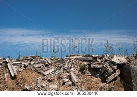 A Pile Of Gray Concrete Debris Against A Blue Textured Sky With Feathery White Clouds. Background