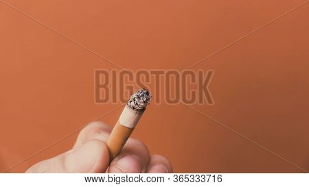 Smoldering Cigarette In His Hand On An Orange Background
