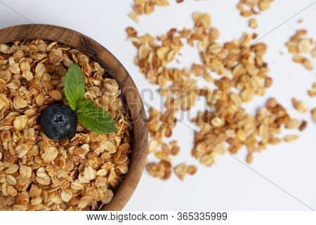 Top View On A Wooden Bowl With Homemade Granola Or Granola With Blueberries And Mint. Place For Text