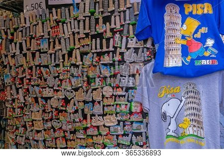 Pisa, Tuscany, Italy, April 05, 2019: Magnets And Shirts In A Souvenir Shop, Showing The Famous Lean