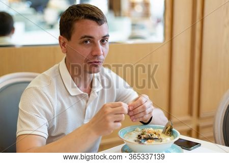 A Man Is Eating An Oriental Asian Dish. An Adult European Man Of 30-35 Years Old Is Eating Seafood S