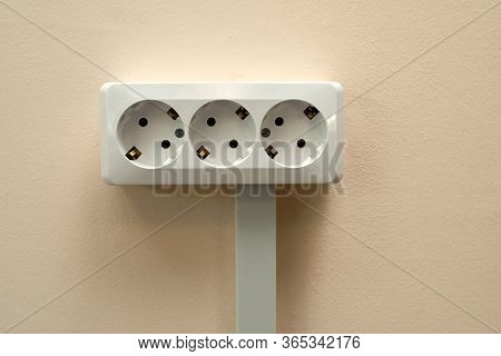 A Block Of White Outlets Consisting Of Three Standard Outlets With Grounding