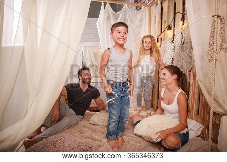 Young Family Parents With Children Daughter And Son Have Fun At Home Fooling Around, Playing And Spe