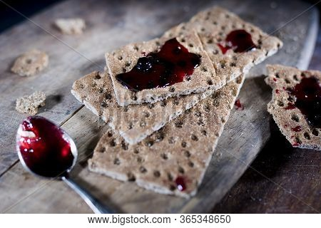 Open Jar With Blackcurrant Jam On A Wooden Cutting Board. Dry Biscuits Spread With Jam, Crumbs And A