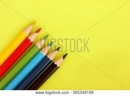 Colored Pencils On Yellow Background. 6 Colors Black, Blue, Blue, Green, Red, Yellow. Pencils Are We