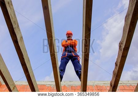 Roofer Carpenter Builder Working On Roof Structure On Construction Site. Construction Worker On Cons