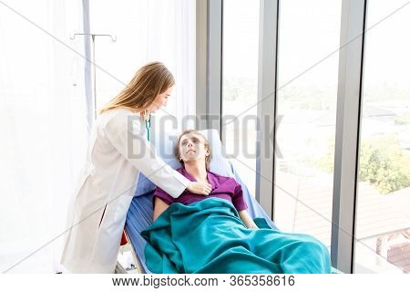 Doctor Examining The Symptoms Of A Patient Is Stomach Ache Patient Sitting In Bed.