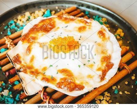 Baked Scallops With Cheese On The Scallop Shell With Topping Made Of Orange Roe.