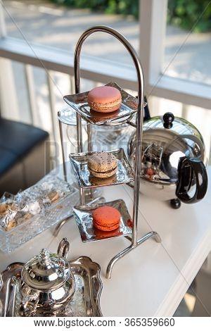 Macaron And Teapot On The White Table.