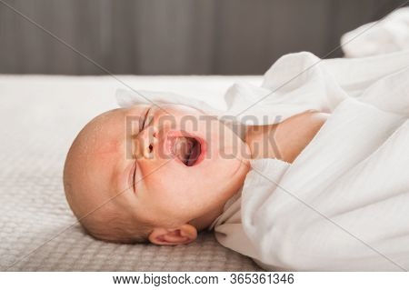 Newborn On The Bed. Crying, Screaming Baby Close Up And Copy Space. Baby Smile And Colic In Newborns