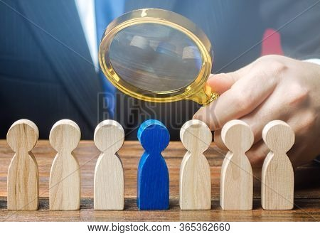 Businessman Holds A Magnifying Glass Over A Worker. Recruitment Concept. Hiring, Hire. The Best Empl