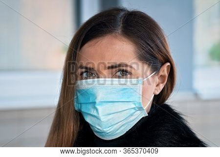 Young Woman Wearing Disposable Blue Virus Face Mouth Nose Mask. Coronavirus Covid-19 Outbreak Preven
