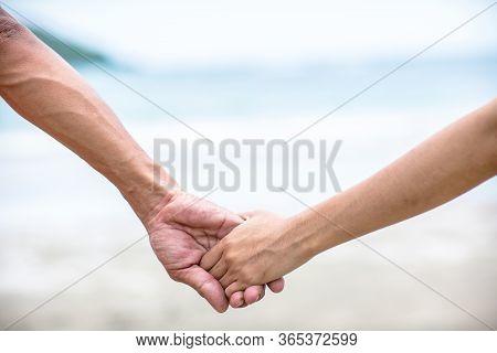 Summer Couple Holding Hands At Sunset On Beach. Romantic Young Couple Enjoying Sun, Sunshine, Romanc